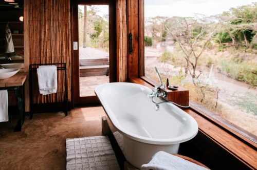 Villa resort bathroom luxury white bathtub with forest view through bay window - African Boho style Safari camp lodge interior decoration with wooden bamboo wall