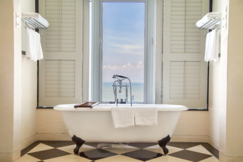 Luxury classic bathtub in bathroom with relaxing ambient and window with scenic sea view