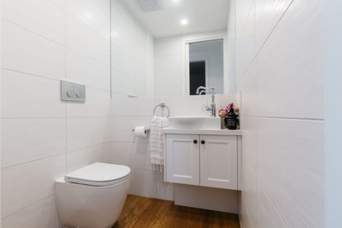 Bright white contemporary powder room in an Australian home