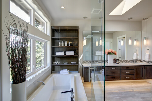 Contemporary master bathroom features a dark dual vanity cabinet , glass walk-in shower, drop-in tub and open cabinets filled with shelves. Northwest, USA