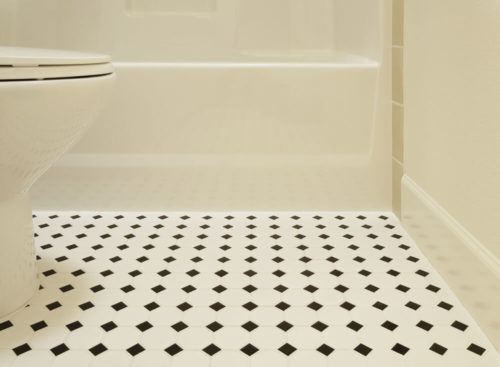 A white acrylic bathtub and porcelain toilet of a bathroom are sitting on a diamond patterned vinyl flooring in a bathroom. Horizontal shot.