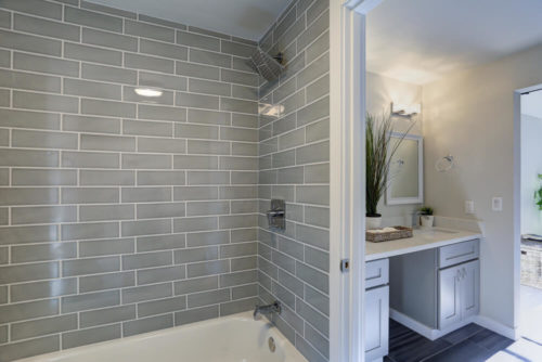Warm and clean bathroom boasts grey glass tile shower surround and double vanity cabinet with granite countertop.