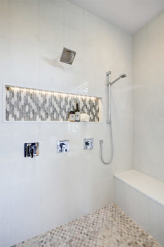 Stunning walk-in shower features white tile surround, shower niche fitted with mosaic gray tiles flanked by hand held shower head and wall-mounted rain shower head. Northwest, USA