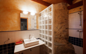 Nice warm interior ofbathroom in a rustic style in country house or hotel. Wooden beams and walls made of natural stone. Mediterranean style.