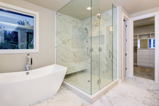 Sleek bathroom features freestanding bathtub atop marble floor placed in front of glass shower accented with rain shower head and gray and white marble surround.