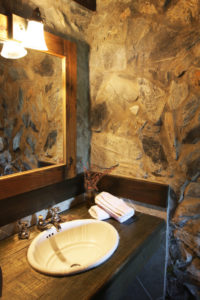 A DSLR photo of a rustic and cozy bathroom with stone walls.
