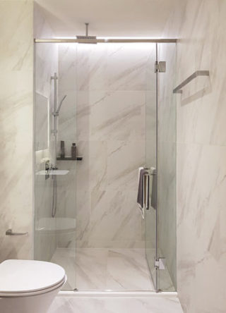 Modern luxury style bathroon interior decoration, Clear glass shower enclosure frameless design with white calacatta marbe tiles backdrop.