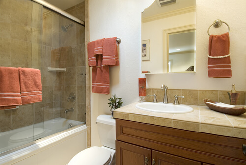 modern bathroom, shower with glass doors and tile,sink and toilet, matching towels
