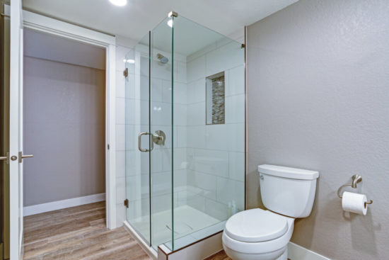Elegant bathroom with glass shower and hardwood floor.