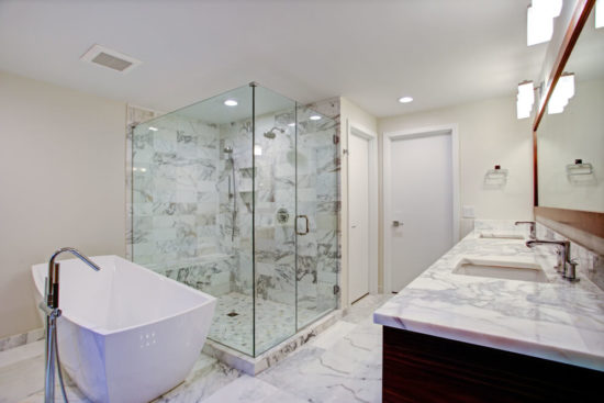 Sleek bathroom features freestanding bathtub paired with floor-mounted faucet atop marble floor placed in front of glass shower accented with gray marble surround.