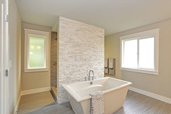 Amazing master bathroom accented with stone wall walk-through shower and freestanding bathtub over Porcelain tiled floor.