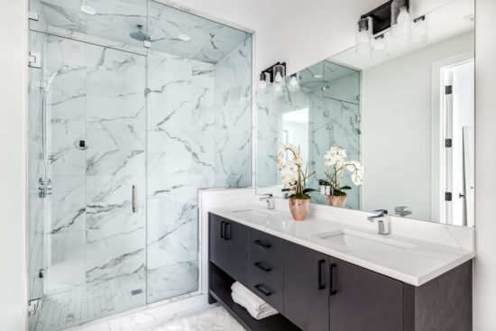 CHICAGO, IL, USA - FEBRUARY 8, 2020: A beautiful bathroom with a dark vanity and white granite counter top. A plant and towels sit on the vanity. The shower is lined with marble tiles. Lights off.