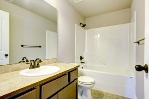New home bathroom interior with shower and bath combination, wood cabinet and toilet.