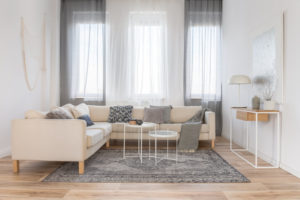 White industrial coffee tables in bright living room interior with big corner couch