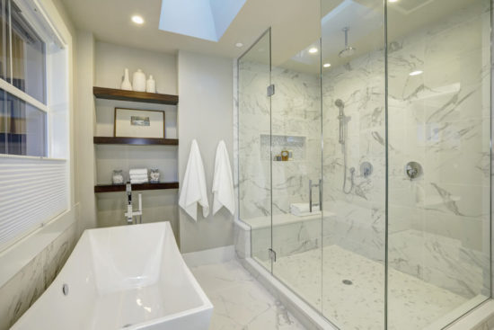 Amazing white and gray marble master bathroom with large glass walk-in shower, freestanding tub and skylights on the ceiling.