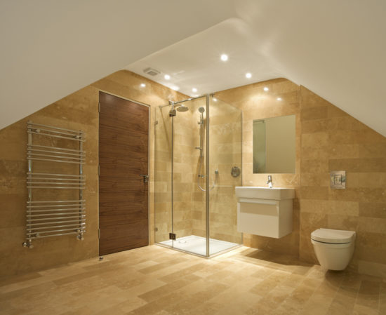 This is an image of a bathroom in the attic of an expensive new home. A shower unit sits in the centre with fixed and hand shower. To the left of the solid walnut door is a modern towel radiator. To the right of the shower is a handwash basin and toilet. The walls and flooring are lined with natural stone.