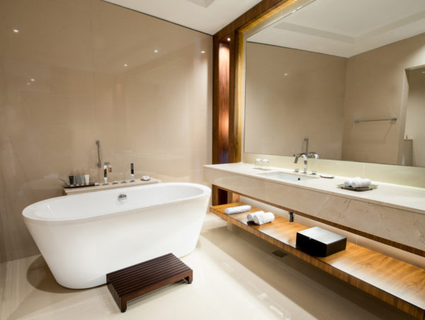 A modern luxury bathroom suite with a large mirror