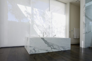 """Low angle view of a modern bathroom with stand-alone marble clad tub, hardwood floor and vertical shades."""