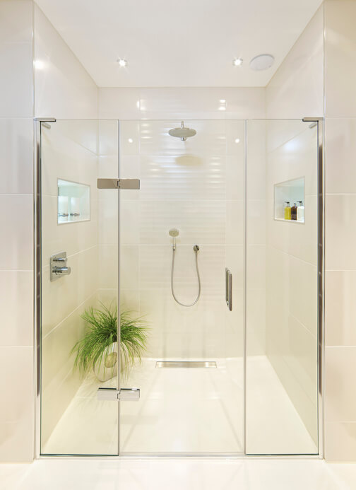 "a fabulous shower room in a luxury penthouse apartment. A large area recessed deep into a wall is accessed through glass doors. On either side of the shower area are decorative recesses for ornaments, such as candles to the left, and liquid soap to the right. A decorative plant is located in the left corner. A large showerhead (""rainfall"") is set in the back wall whilst below is a hand shower."