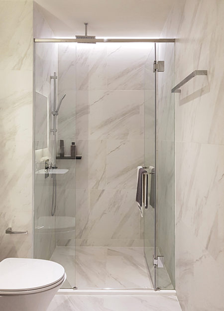 This is an image of a Modern luxury style bathroon interior decoration, Clear glass shower enclosure frameless design with white calacatta marbe tiles backdrop.