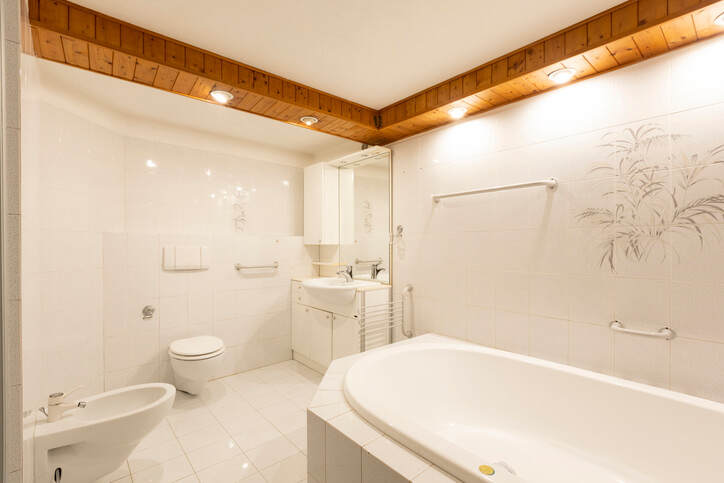 Bathroom with white tiles and wooden ceiling. Elegant. No one inside