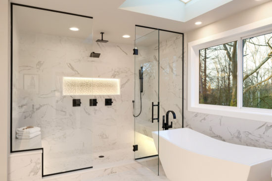 This is an image of Detailes of the larhe walk in shower with white marble and mosaic, light. Three handles, shower head in dark brass.and free standing modern tub.