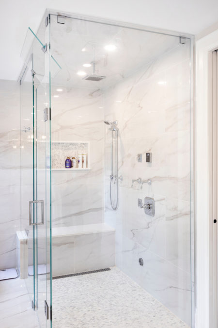 This is an image of a white, clean, bright and spacious custom designed bathroom covered in marble tiles in Burlington, with overhead shower panel.