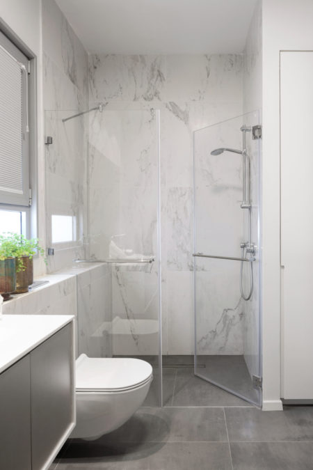 This is an image of a Bathroom with elongated sink, shower head, rolled white towels, small floor tiles, cozy lighting, scroll curtain