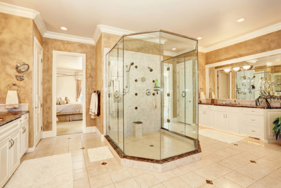 This is an image of a Beautiful luxury marble bathroom interior in beige color. Large glass walk in shower and two vanity cabinets.