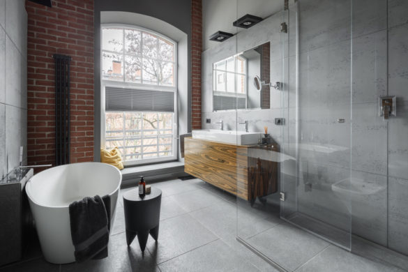 This is an image of an Industrial style bathroom with oval bathtub and walk in shower