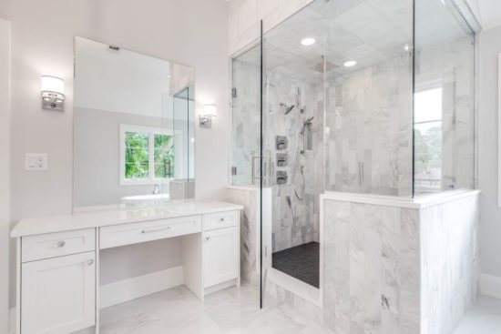 This is an image of a large, luxurious bathroom with a walk in shower lined with marble tiles. A white vanity sits next to the shower with a standalone tub is seen through the mirror