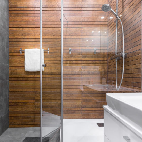 This is an image of a Modern bathroom with walk in shower and wooden effect tiles