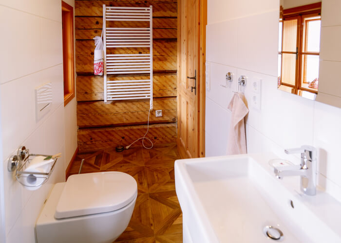 Interior with modern white bathroom with wood design. Home with mirror, sink and toilet bowl. Hotel bath room. House with toilet furniture and decor. Wall and floor on background. Wooden decoration.