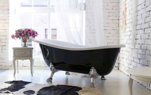 Classic claw foot black bathtub beside the window