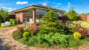 Moscow Region - Aug 24, 2019: Landscape design at residential house. Landscaping with paved path in home garden. Panoramic view of landscape garden in backyard. Nice landscaped place in summer.