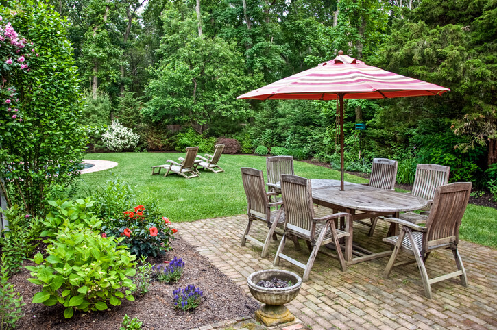 An example of extensive and lush landscaping with a backyard brick patio.