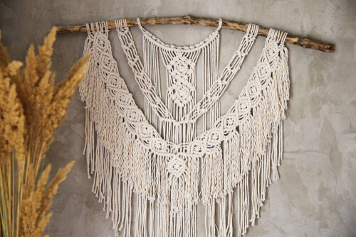 Wall panel in the style of Boho made of cotton threads in natural color using the macrame technique for home decor and wedding decoration. Beautiful boho macrame wall panel will add a cozy atmosphere
