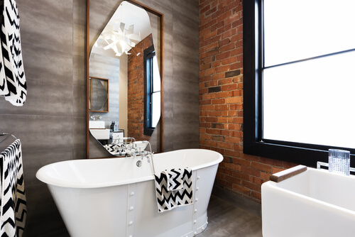 Horizontal version freestanding vintage style white bath tub in renovated warehouse apartment