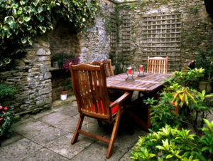 Small secluded garden patio, walls around, wooden tables and chairs