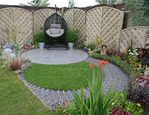 A garden design based on flowing curves around a patio area in a small urban garden