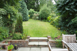 Terraced and landscaped back garden in England UK with patio, grass and stone steps