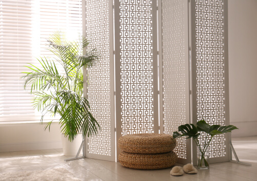 Stylish room interior with white folding screen room divider and plants