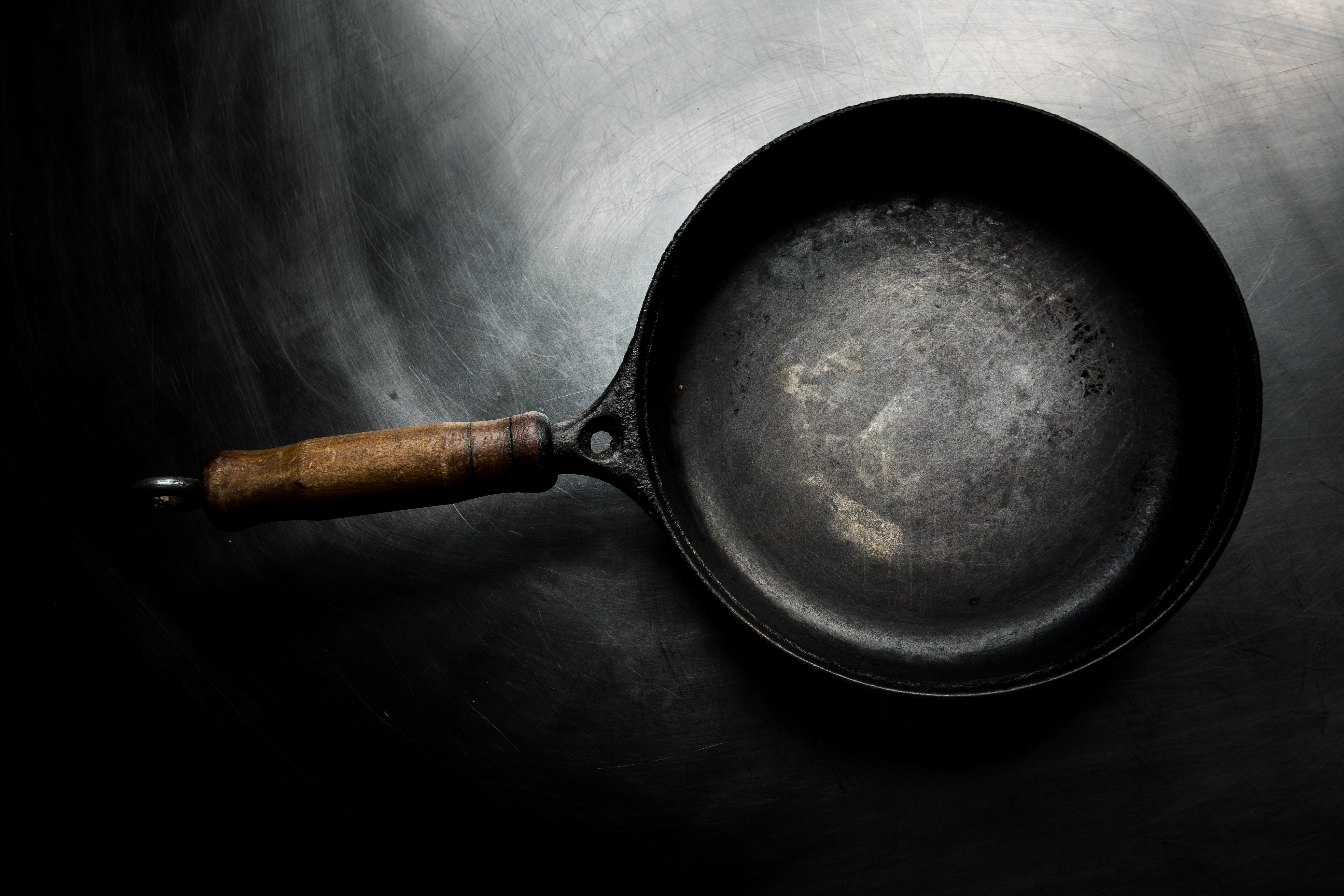 Black used carbon steel pan with wooden handle on black metallic surface
